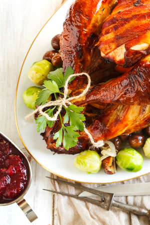 turkey bacon: Roasted turkey with bacon and garnished with chestnuts and brussels sprouts. Prepared for Thanksgiving or Christmas dinner.