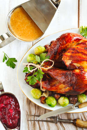 feast: Roasted turkey with bacon and garnished with chestnuts and brussels sprouts. Prepared for Thanksgiving or Christmas dinner.