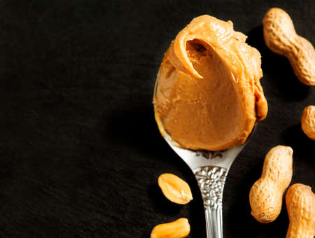 peanut butter: Peanut butter in spoon over black background