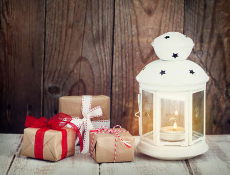 Christmas gifts and candle on wooden background
