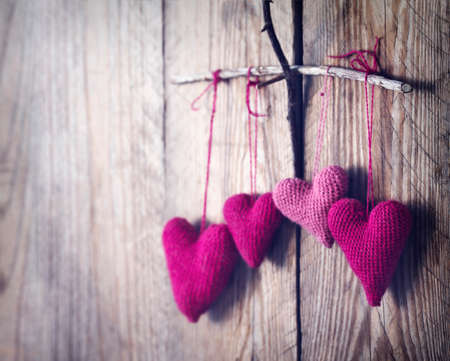 Crochet rosa Herzen auf hölzernen Hintergrund. getöntes Bild