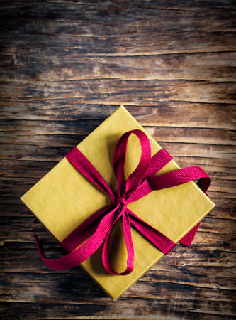 Gift box with bow on wooden background. Selective focus