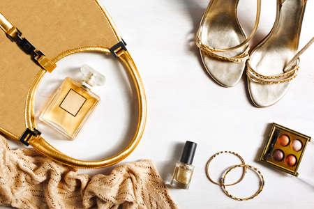 Zestaw damski akcesoriów mody w złotym kolorze na tle drewnianych: Buty torebka, perfum i kosmetyków