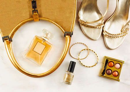 Womens set of fashion accessories in golden color on wooden background: shoes, handbag, perfume and cosmetics Stock Photo