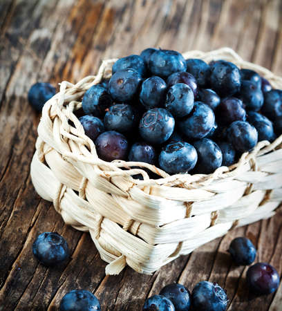 Fresh blueberries in basket on wooden background