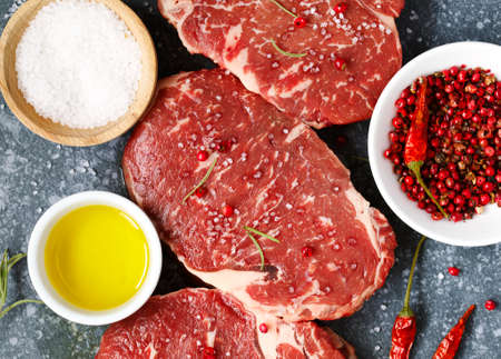 Raw fresh meat Ribeye Steak with rosemary, pepper and sea salt on stone background.