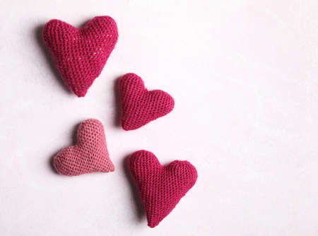 Crochet hearts on pink background. Valentine's Day concept, copy space