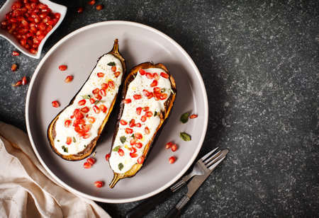 Baked eggplants with garlic yogurt sauce and pomegranate, top view, copy space Imagens