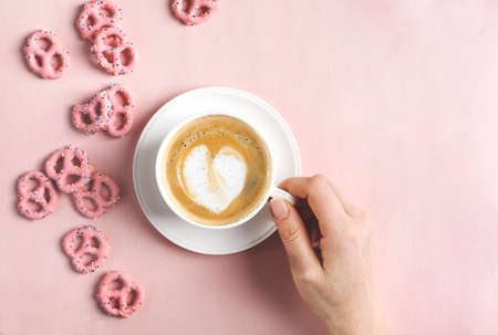 Female hands hold cup of coffee with art heart shape on pink background. Love concept. Flat lay, top view Stock Photo