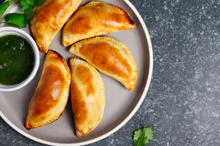Empanadas with chimichurri sauce. Traditional Latin American cuisine. Top view, copy space