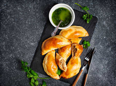 Empanadas with chimichurri sauce. Latin American tradition cuisine. Top view, copy space