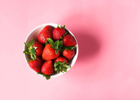 Strawberries in bowls on pink background, top view, copy space