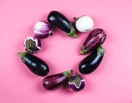 Fresh eggplants of different color and variety on a pink background, top view, copy space