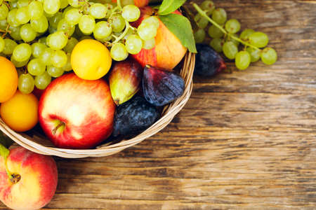 Autumn fruits in basket on wooden background witn copy space 版權商用圖片