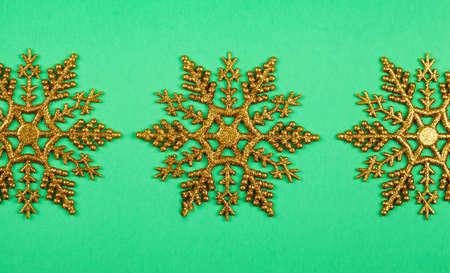 Christmas golden osnowflakes on green background. Christmas decoration. Christmas card.