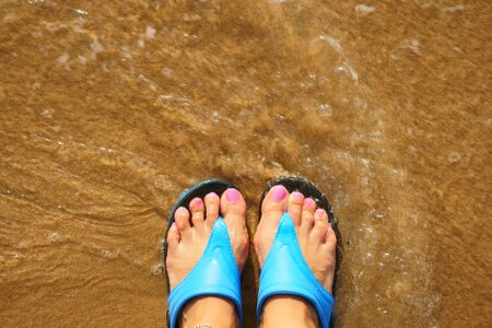 woman foot: female foot in flip flops on the beach