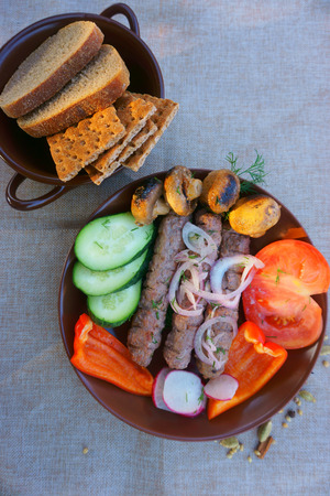 grilled meat, vegetables on a dish on the table