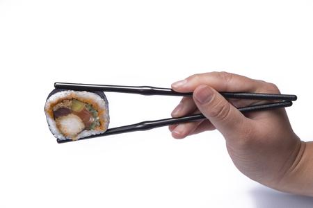 hand holding chopsticks eating sushi om white background Stock Photo