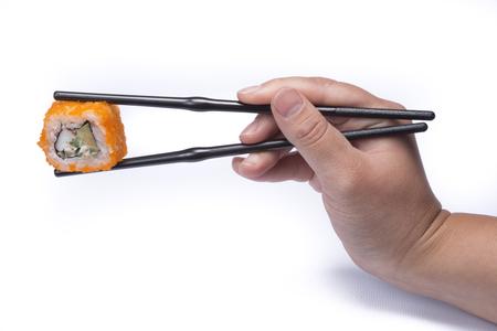 tumb: hand holding chopsticks eating sushi om white background Stock Photo