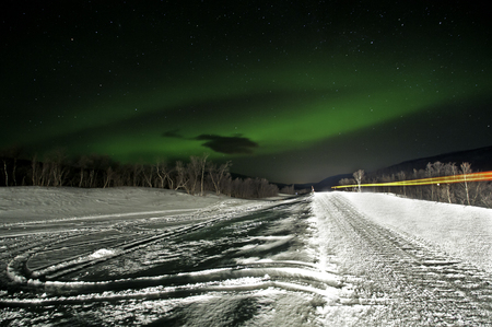 northern light: Northern green light at cold snowy mountain and car passing by Norway