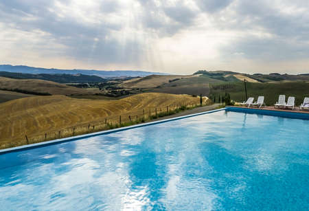Swimming pool with view at beautiful landscape of Tuscany, Italy