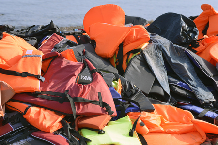 skala: LESVOS, GREECE OCTOBER 24, 2015: Lifejackets, rubber rings an pieces of the rubber dinghys discarded on a beach near Molyvos. Eftalou and Skala Sikaminia. Lesvos has been a hot spot for migrants and refugees arriving in inflatable boats from Turkey.