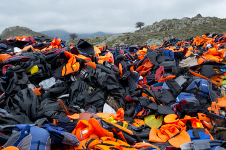 dinghies: LESVOS, GREECE February 21, 2016: Lifejackets, rubber rings an pieces of the rubber dinghies left by refugees are making a mountain in Eftalou. Lesvos has been a hot spot for refugees.