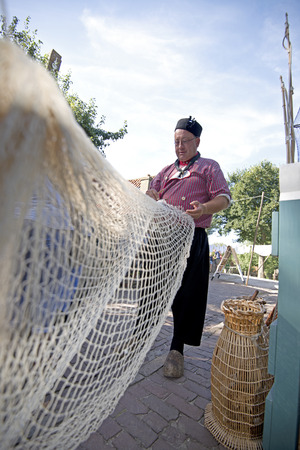 Enkhuizen, The Netherlands,10-09-2016: Fisherman fixing his nets