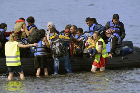 LESVOS, GRIEKENLAND 12 oktober, 2015: Vluchtelingen die in Griekenland in smerige boot van Turkije aankomen. Deze Syrische, Afghaanse en Afrikaanse vluchtelingen landen hun boot aan de noordkust van Lesbos in de buurt van Molyvos, Eftalou en Skala Sikaminia Redactioneel