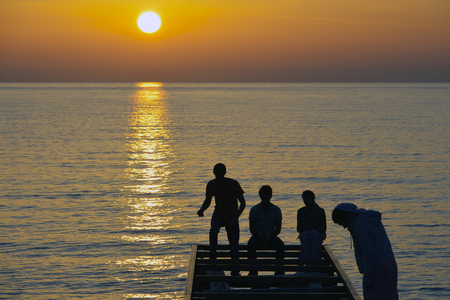 teenagers playing on pier in sunset, Lesvos Greece Editorial