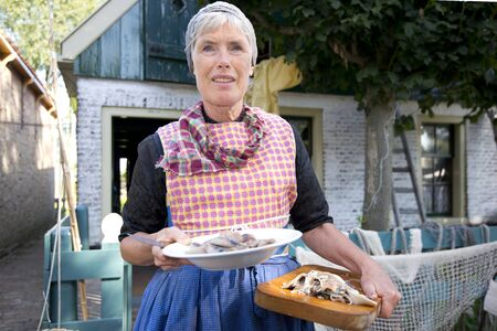dutch girl: The Netherlands, Enkhuizen,10-09-2016: Woman with raw herring an traditional meal