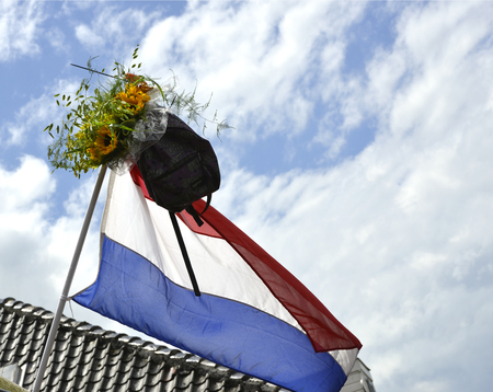 dutch: A schoolbag and a bouquet of sunflowers are hanging from a Dutch flag to show that the owner has finished school.