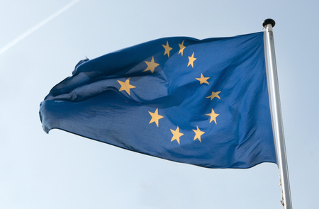 The flag of the European Union as it waves in the wind. Its dark blue colour is in beautiful contrast to the light blue sky. Stock Photo