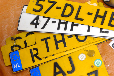 Various Dutch license plates stacked on a table.
