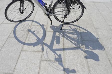 De schaduw van een fiets op de stoep