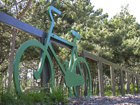 Een groene fiets tegen een hek in het bos.