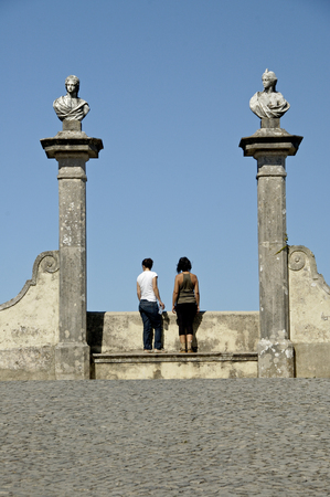 busts: Sintra Portugal, 27-September-2007: Two people looking at the view from in between two ancient busts in Sintra.