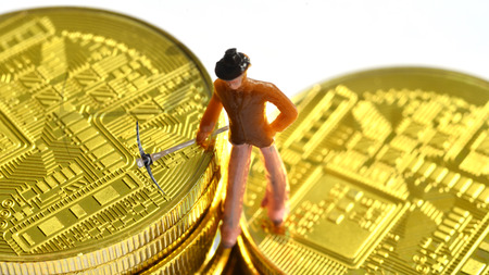 a little man is mining on a pile of bitcoin