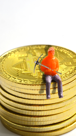 a little man is resting from mining on a pile of bitcoin Stockfoto