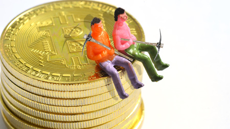 a little men are resting from mining on a pile of bitcoin