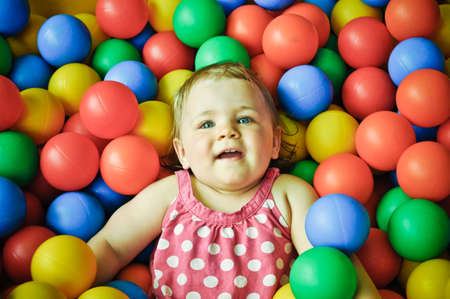 playcentre: Smiling one year old girl swimming in colourful plastic ball pool
