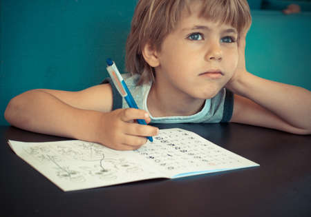 Five year old boy dreaming while doing his math homework
