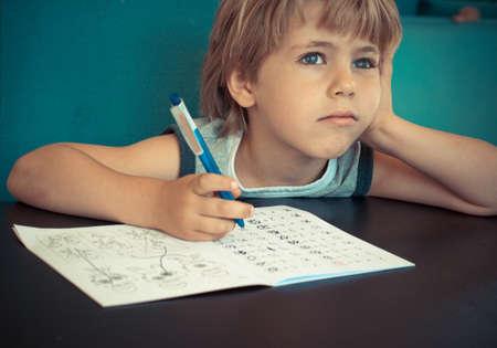 escuelas: Niño de cinco años soñando mientras hacía su tarea de matemáticas