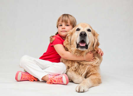 4 year old: 4 year old girl sitting and hugging her big golden retriever dog.