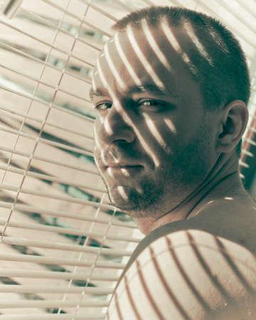 handsom: Hombre Handsom de pie en una ventana de persianas y mirando por encima del hombro hacia atr�s Foto de archivo