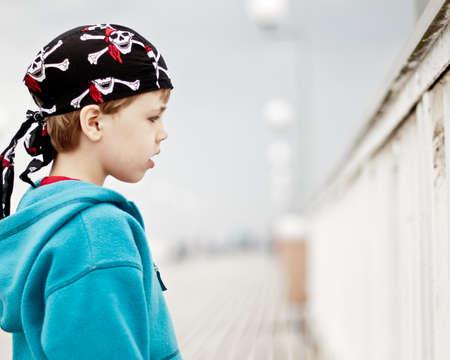 rowdy: Un muchacho joven que llevaba pa�uelo camorrista de pie en un muelle Foto de archivo
