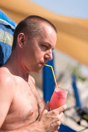 handsom: Handsom man sipping a drink at a hotel swimming pool