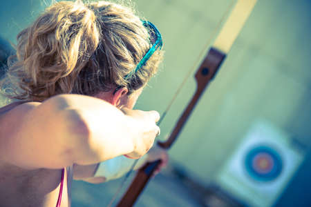 Young woman aiming with a bow 写真素材