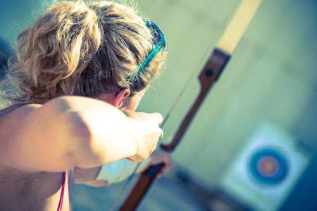Junge Frau mit dem Ziel mit einem Bogen