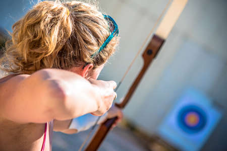 Young woman aiming with a bow Imagens